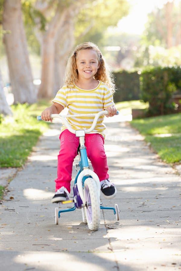 Muchacha que aprende montar la bici en la trayectoria imagen de archivo