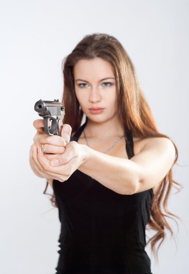 Muchacha que apunta un arma imagenes de archivo