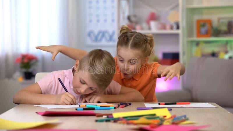 Muchacha que asusta al hermano que estudia en la tabla, hiperactividad del niño, déficit de atención imagen de archivo