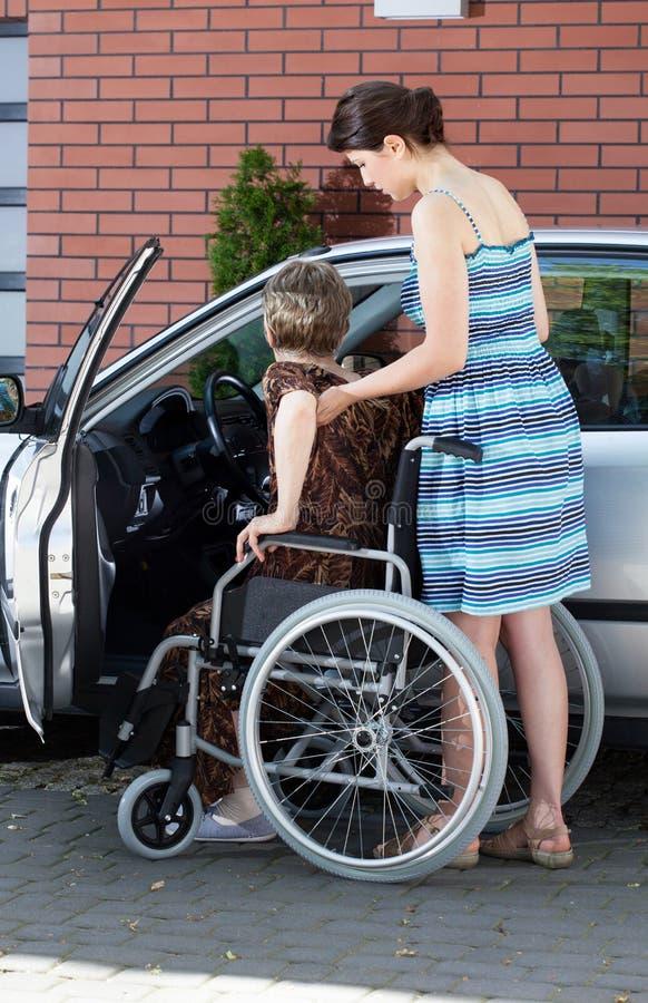 Muchacha que ayuda a la mujer discapacitada que consigue en un coche fotos de archivo libres de regalías