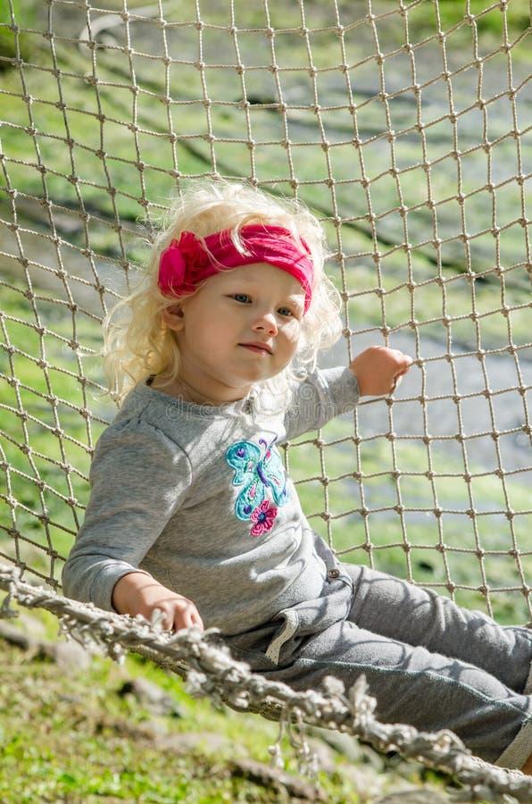 Muchacha que balancea en una hamaca fotografía de archivo