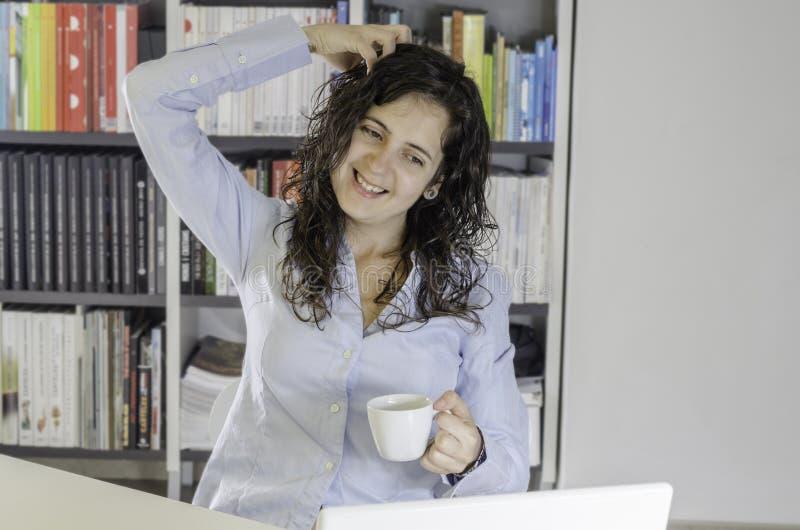 Muchacha que bebe un café en la oficina imagenes de archivo