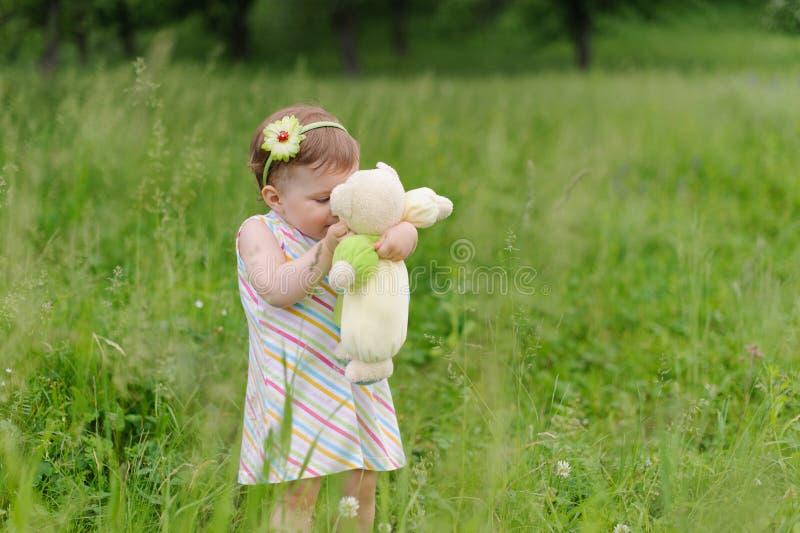Muchacha que besa el oso de peluche fotografía de archivo