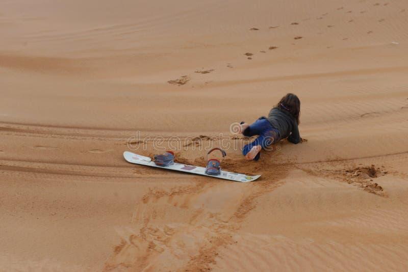 Muchacha que cae de su tablero de la arena foto de archivo