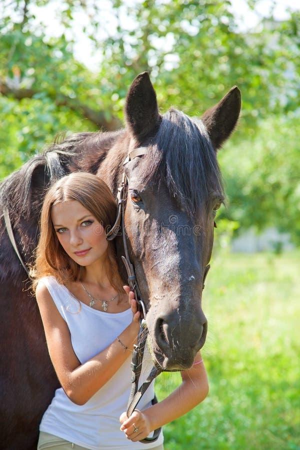 Muchacha que camina en el parque con un caballo imagenes de archivo