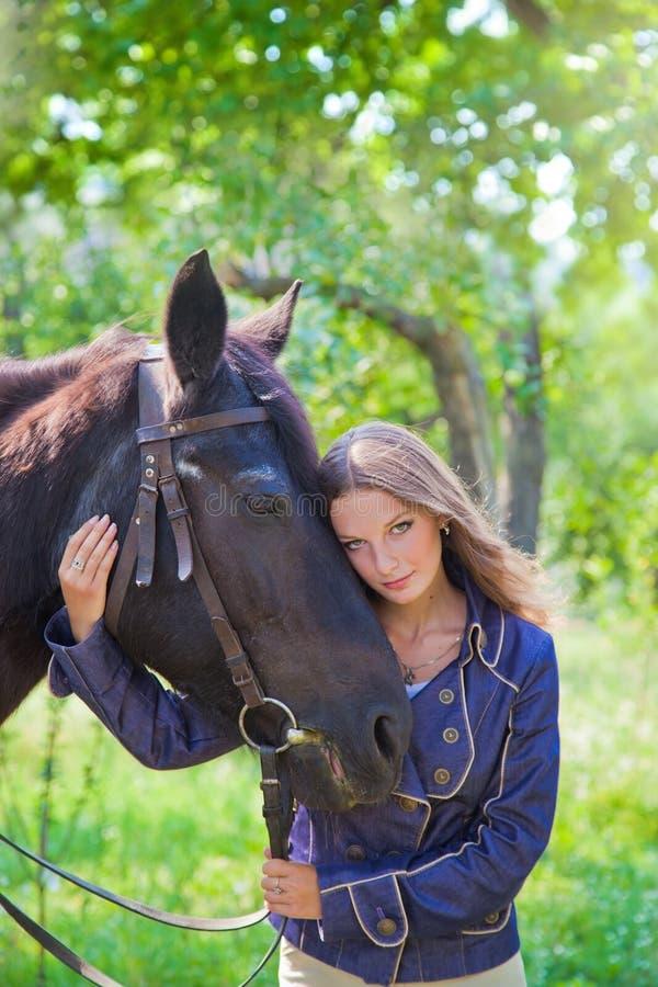 Muchacha que camina en el parque con un caballo imagen de archivo libre de regalías