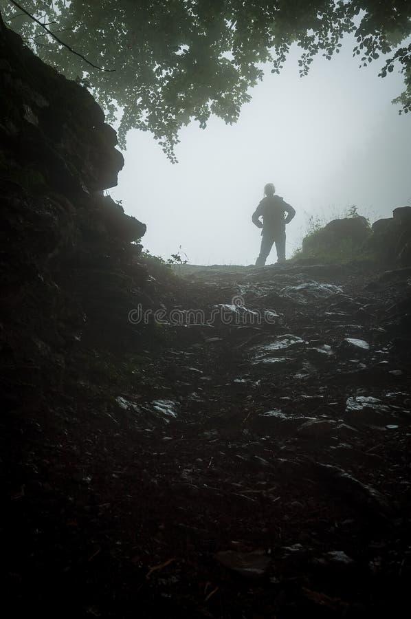Muchacha que camina en las montañas durante el tiempo lluvioso imagenes de archivo