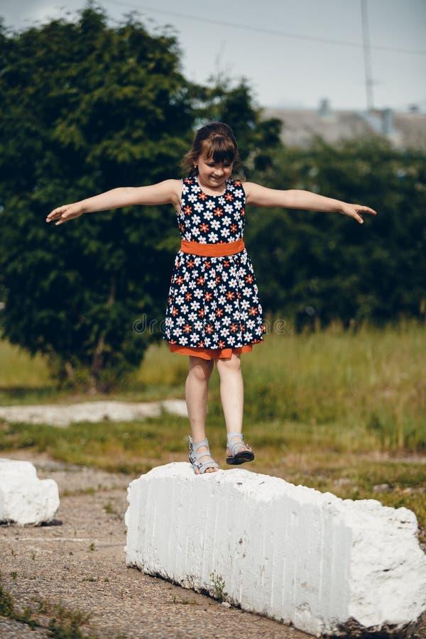 Muchacha que camina en un vestido que aumenta sus manos fotos de archivo libres de regalías