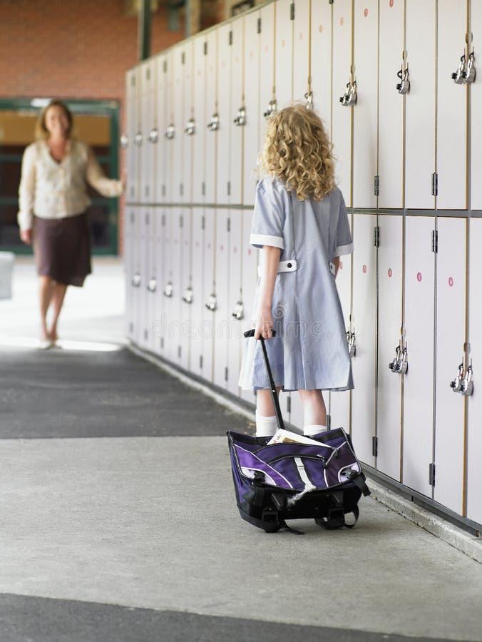 Muchacha que camina hacia madre en pasillo de la escuela fotografía de archivo libre de regalías