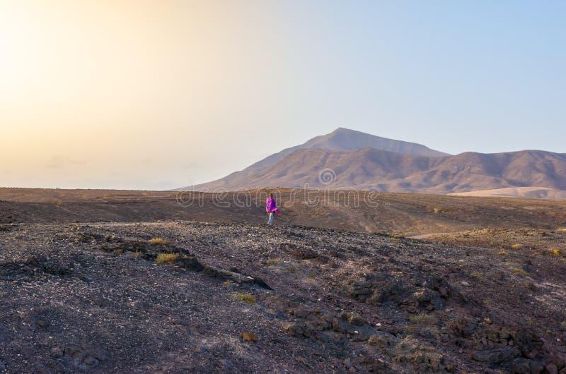 Muchacha que camina a través del desierto en la puesta del sol imagen de archivo