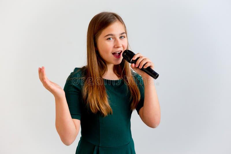 Muchacha que canta con un micrófono imagenes de archivo