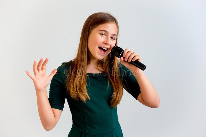 Muchacha que canta con un micrófono imágenes de archivo libres de regalías