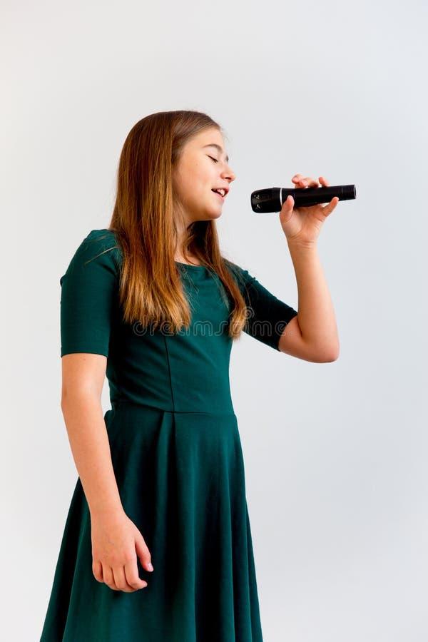 Muchacha que canta con un micrófono fotografía de archivo libre de regalías