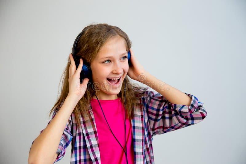 Muchacha que canta en auriculares imagen de archivo