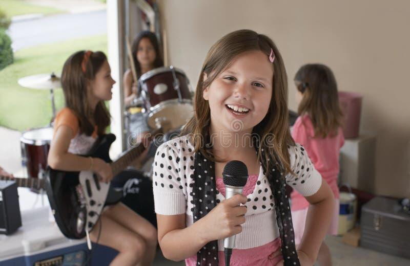 Muchacha que canta en el micrófono con los amigos que tocan el instrumento musical fotos de archivo libres de regalías