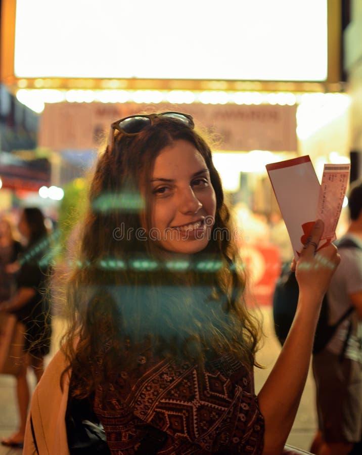 Muchacha que celebra boletos en Broadway fotografía de archivo libre de regalías