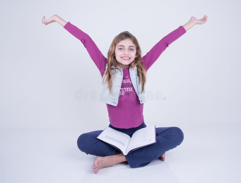 Muchacha que celebra el libro de lectura imágenes de archivo libres de regalías
