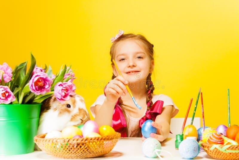 Muchacha que colorea los huevos del este y el conejo lindo cerca imagen de archivo