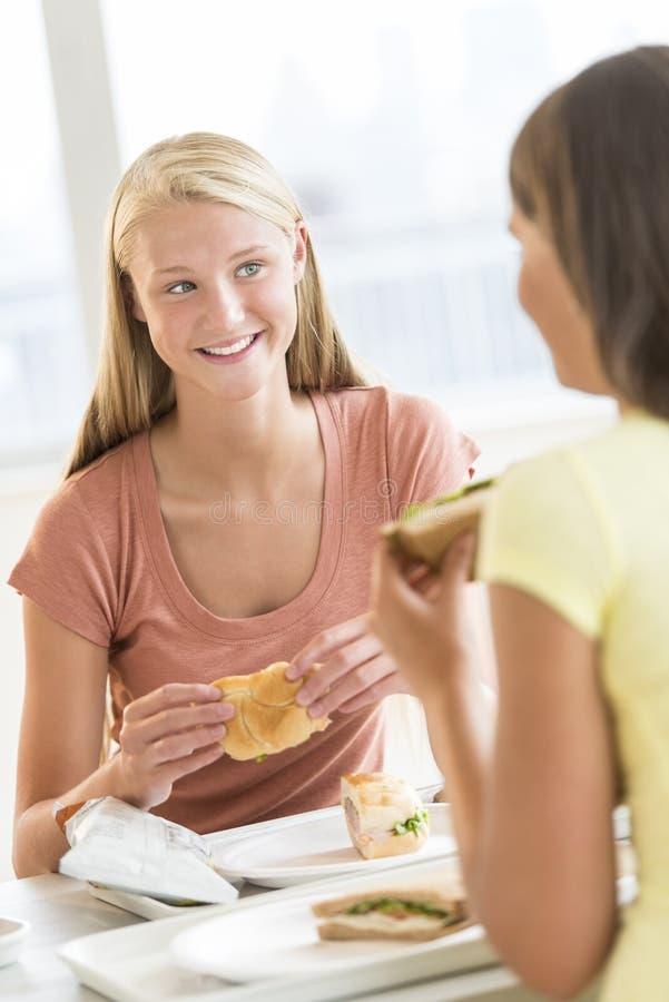 Muchacha que come bocados con el amigo en cantina de universidad fotografía de archivo