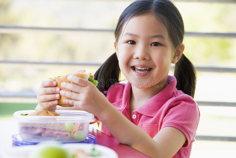 Muchacha que come el almuerzo en el jardín de la infancia fotografía de archivo libre de regalías