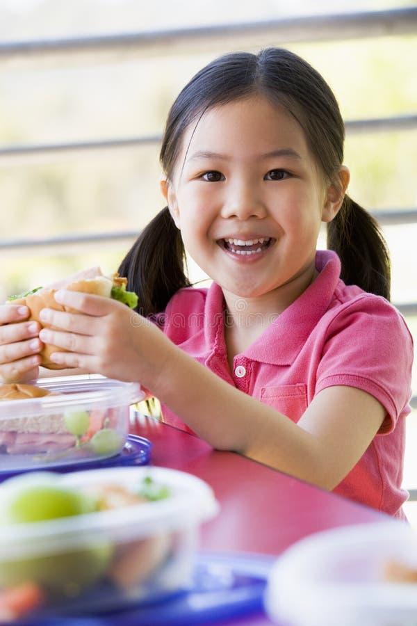 Muchacha que come el almuerzo en el jardín de la infancia fotos de archivo libres de regalías