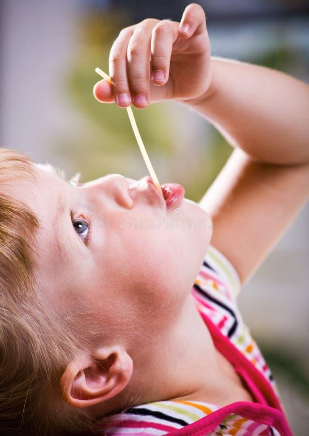 Muchacha que come el espagueti fotografía de archivo