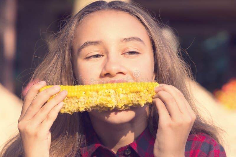Muchacha que come el maíz dulce en la naturaleza imagenes de archivo