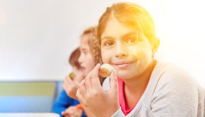 Muchacha que come el plátano como bocado fotografía de archivo libre de regalías