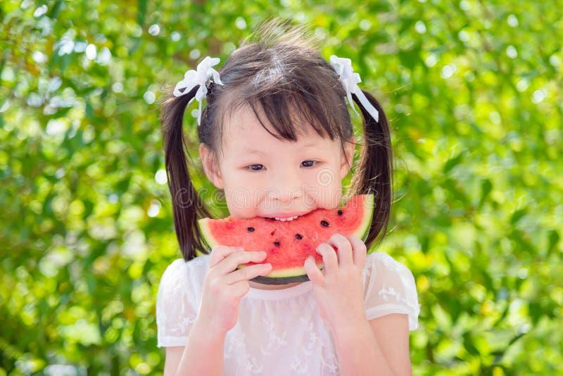 Muchacha que come el watemelon entre la comida campestre en parque fotografía de archivo libre de regalías