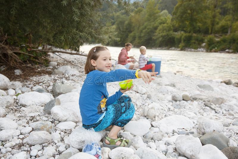 Muchacha que come en naturaleza, teniendo comida campestre con su familia Forma de vida al aire libre, parenting positivo, concep fotografía de archivo