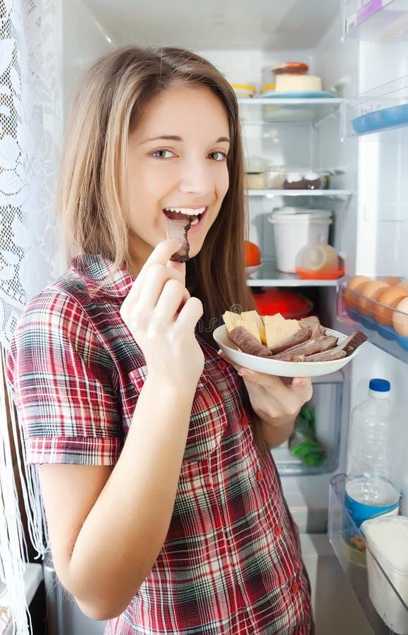 Muchacha que come la carne del refrigerador fotos de archivo