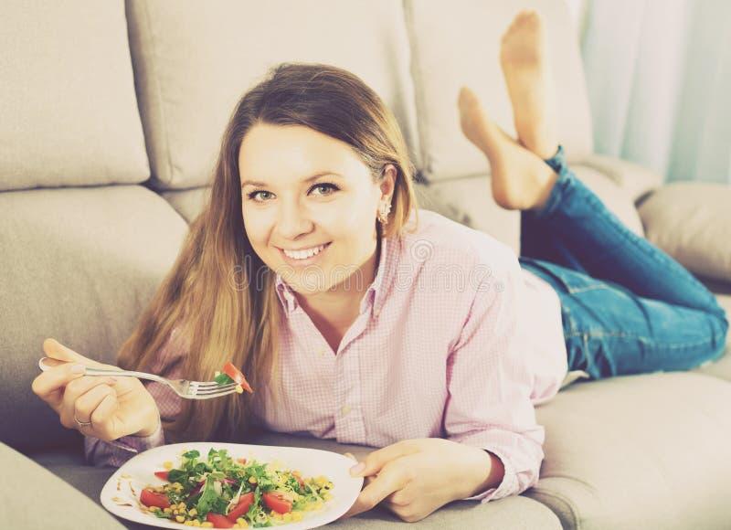 Muchacha que come la ensalada verde imagen de archivo