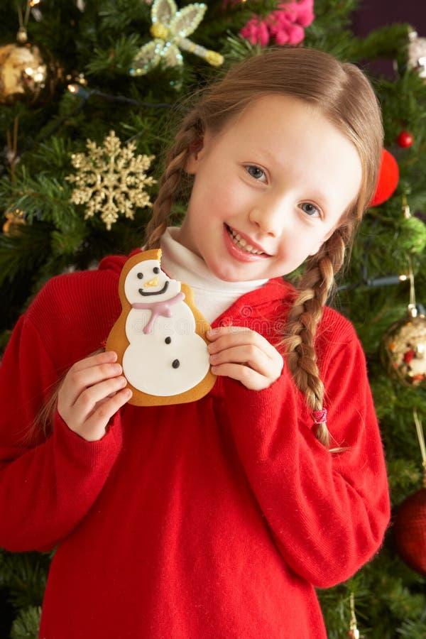 Muchacha que come la galleta delante del árbol de navidad foto de archivo