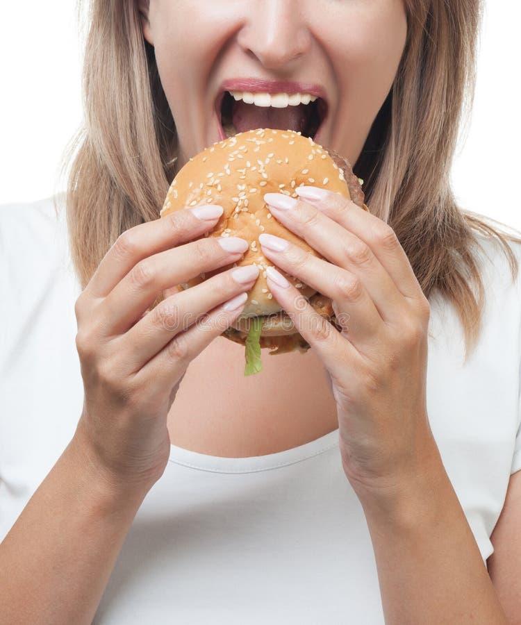 Muchacha que come la hamburguesa en el fondo blanco imagen de archivo