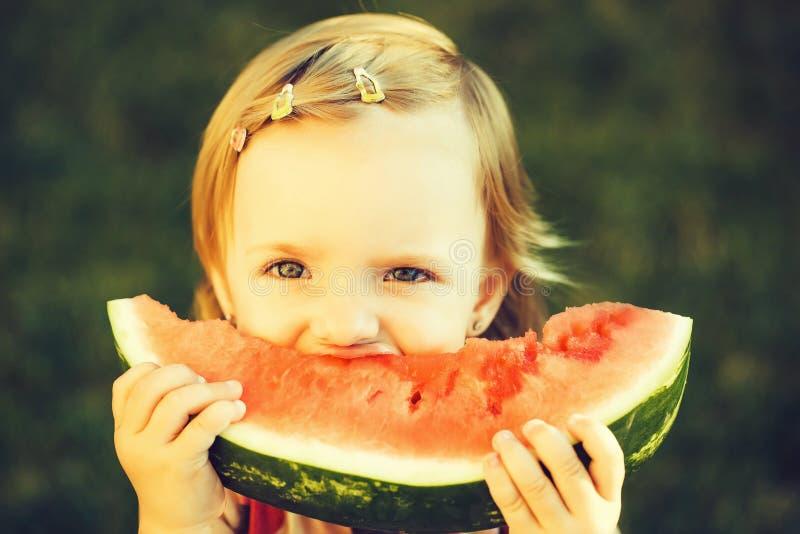 Muchacha que come la sandía roja al aire libre imagenes de archivo