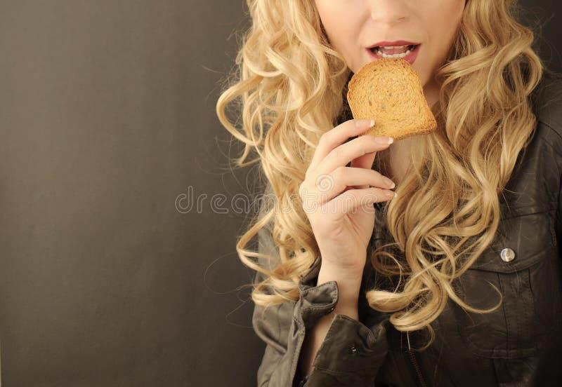 Muchacha que come la tostada foto de archivo