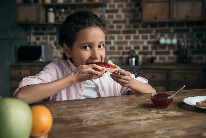 Muchacha que come la tostada con el atasco hecho en casa en casa fotografía de archivo