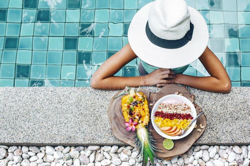 Muchacha que come las frutas exóticas en la piscina foto de archivo libre de regalías