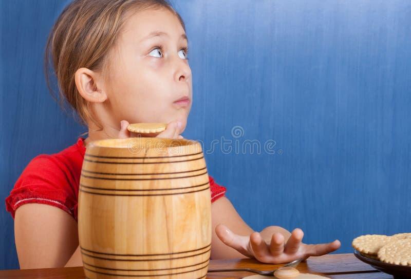 Muchacha que come las galletas y la miel imagen de archivo