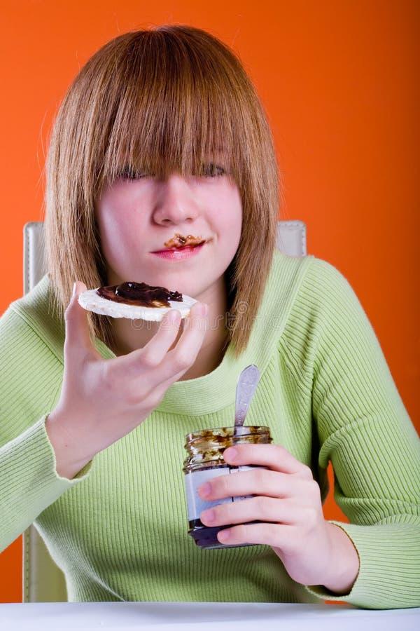 Muchacha que come las obleas imagen de archivo