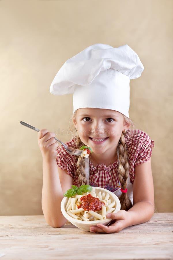 Muchacha que come las pastas con la salsa y la albahaca de tomate fotos de archivo