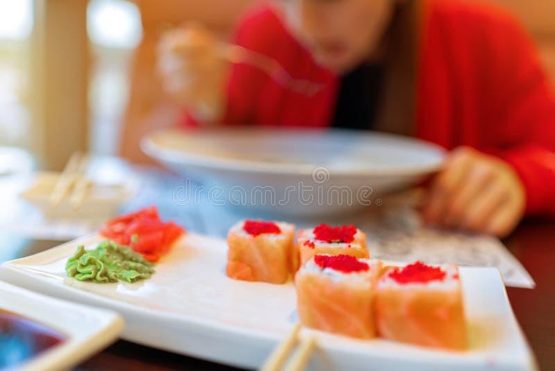 Muchacha que come las pastas y el sushi, falta de definición Sin una cara almuerzo, comida en el restaurante ropa roja, sushi Phi fotos de archivo