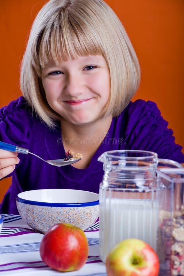 Muchacha que come los copos de maíz imagen de archivo