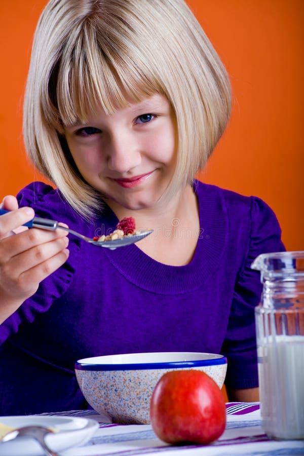 Muchacha que come los copos de maíz foto de archivo