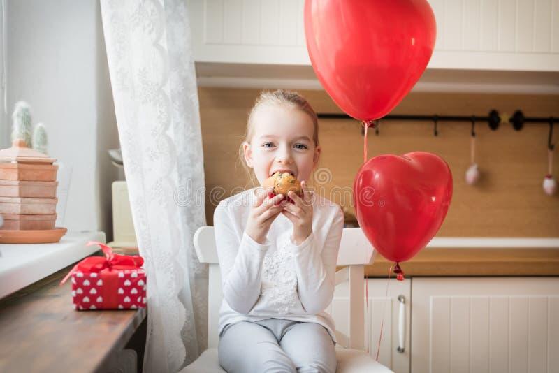 Muchacha que come su magdalena del cumpleaños en la cocina, rodeada por los globos imagen de archivo libre de regalías