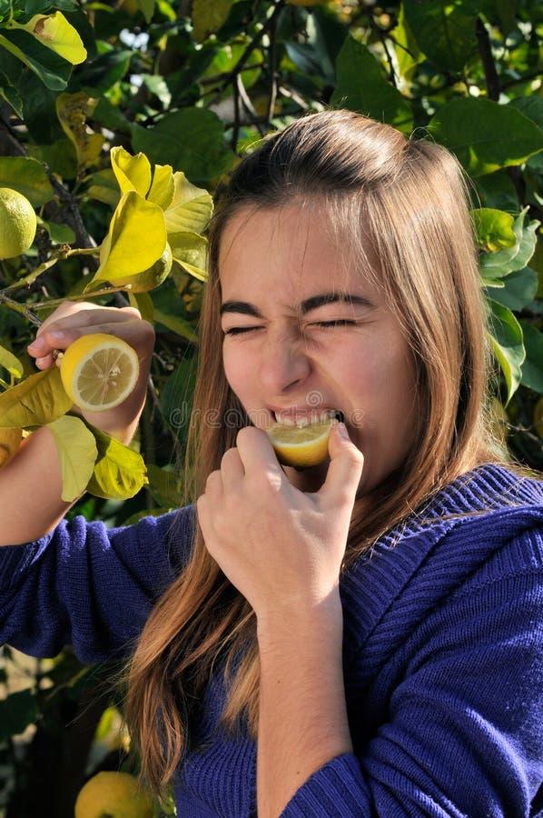 Muchacha que come un limón imágenes de archivo libres de regalías