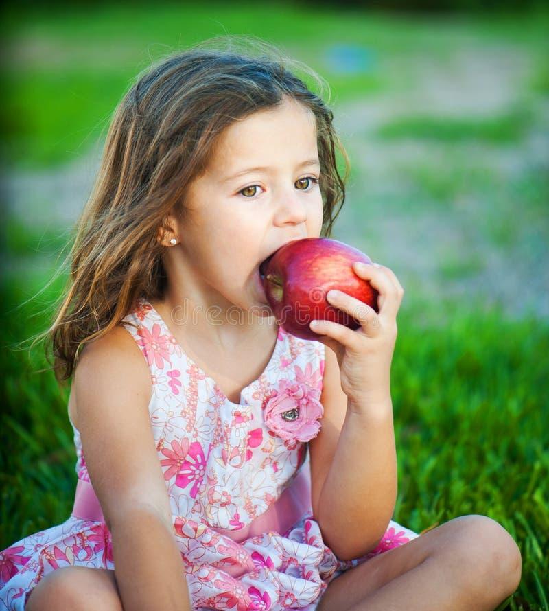 Muchacha que come una manzana imagenes de archivo