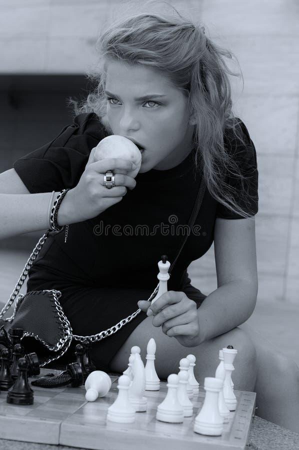 Muchacha que come una manzana mientras que juega a ajedrez fotos de archivo libres de regalías