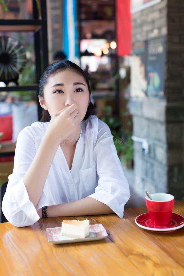Muchacha que come una torta en café imagen de archivo libre de regalías