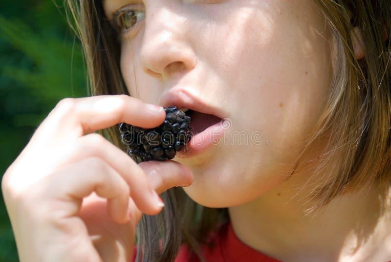 Muchacha que come una zarzamora foto de archivo